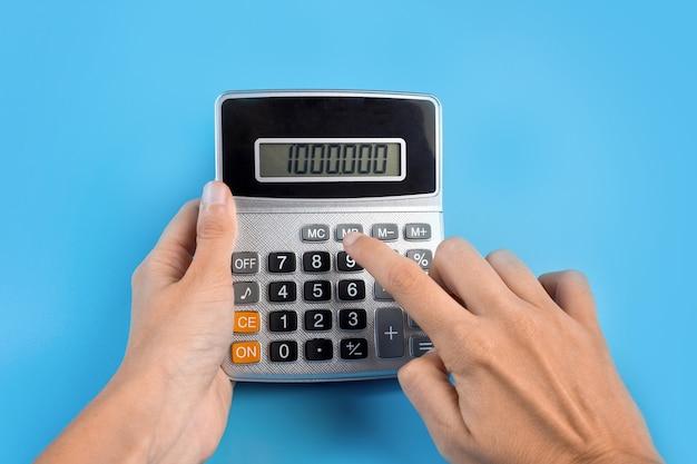 Hände mit einem taschenrechner auf blauem hintergrund. das konzept von finanzen, geschäft, geld, buchhaltung, sparen