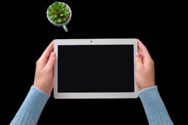 Hände mit einer tablette auf dem tisch. mädchen hält eine tablette in ihren händen.