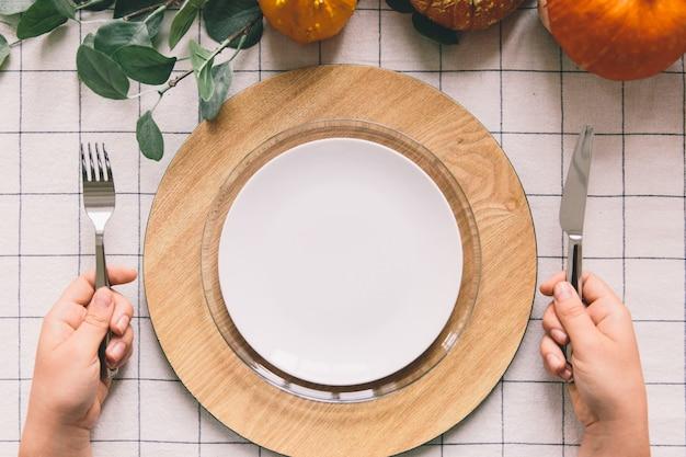 Hände mit gabel und messer, weiße platte auf dem tisch.