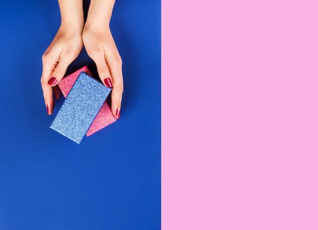 Hände mit geschenkbox auf rosa und klassischem blau