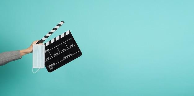 Hände mit grauem anzug und halten schwarzes clapper board oder filmschiefer mit gesichtsmaske. es wird in der videoproduktion, in filmen und in der kinoindustrie auf blauem und grünem oder mintfarbenem hintergrund verwendet.