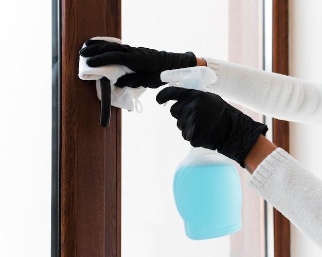 Hände mit handschuhen desinfizieren den fenstergriff