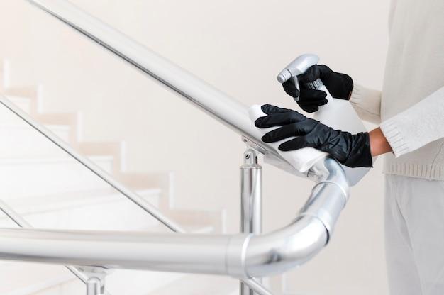 Hände mit handschuhen desinfizieren den handlauf
