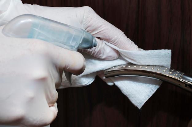 Hände mit handschuhen desinfizieren den türgriff