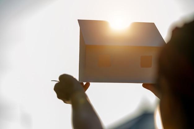 Hände mit hausmodellkonzept geld sparen für haus und immobilien.