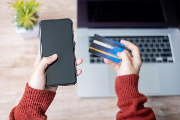Hände mit kreditkarte und gadgets für online-einkäufe