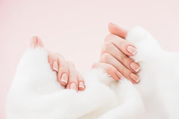 Hände mit maniküre, die tuch hält
