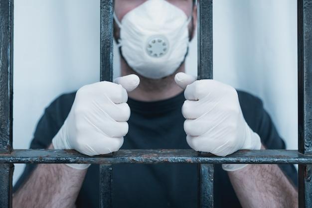 Hände mit medizinischen handschuhen auf stangen. isolierter mann mit operationsmaske greift nach den balken des fensters