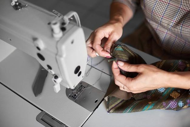 Hände mit nadel zusammennähen kleidungsstück details vor dem nähen