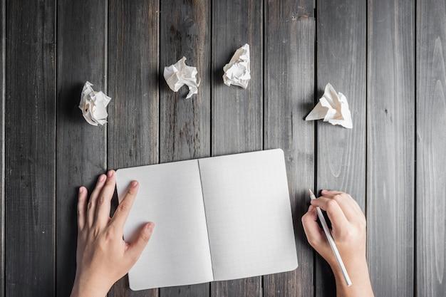 Hände mit notizblock und papierkugeln