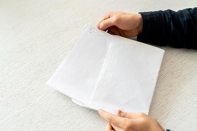 Hände mit papier mit text und legen sie es in den konvertiten, um den brief zu senden