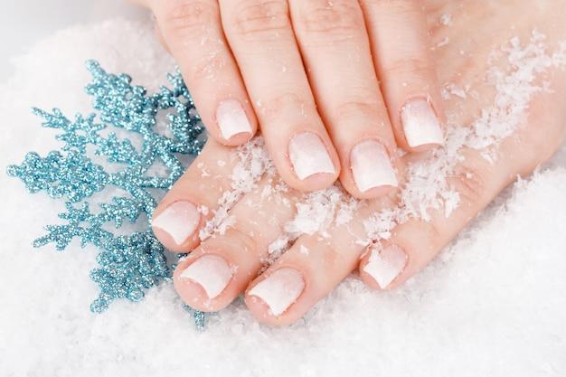 Hände mit schnee und schneeflockennahaufnahme