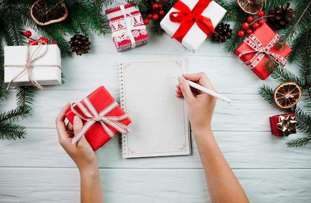 Hände mit sketchbook nahe weihnachtszweig