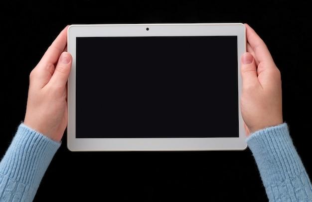 Hände mit tablette auf dem tisch. eine frau hält eine tablette in den händen.
