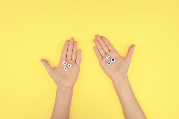 Hände mit würfeln auf gelbem grund.