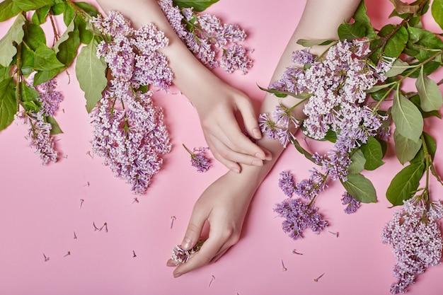 Hände naturkosmetik frauen, leuchtend lila lila blumen in der hand mit hellem kontrast make-up, handpflege