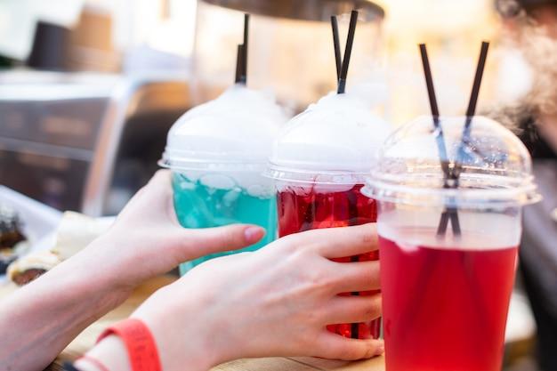 Hände nehmen ein mehrfarbiges fruchtgetränk mit austretendem dampf