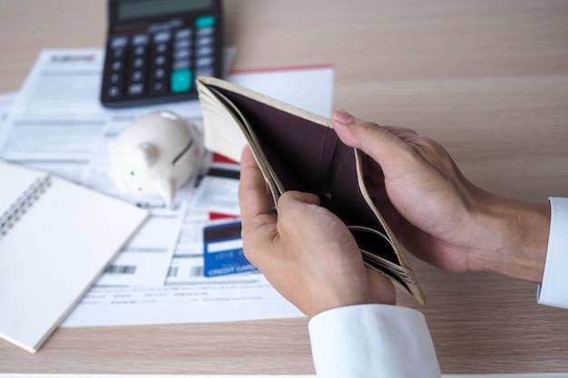 Hände öffnen den leeren geldbeutel, nachdem sie die kosten von der kreditkarte und von der rechnung berechnet haben