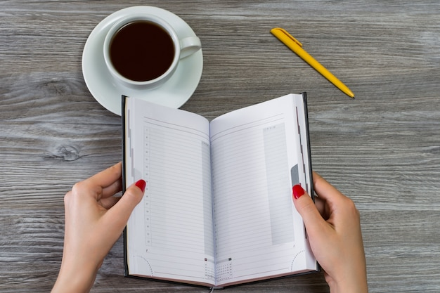 Hände öffnen notizbuch tasse tee und stift