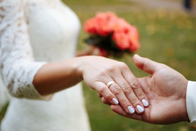 Hände ohands von jungvermählten mit eheringen und einem hochzeitsstrauß.