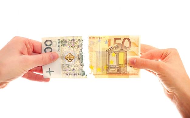 Hände reißen polnischen zloty und europäische note auf weißem hintergrund