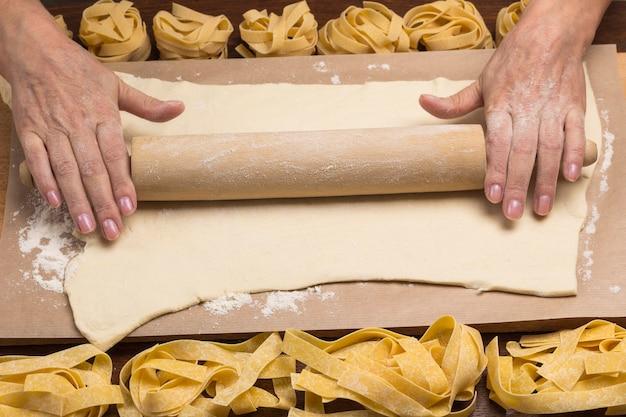 Hände rollen den teig mit einem nudelholz aus. prozess der herstellung von kochnudeln