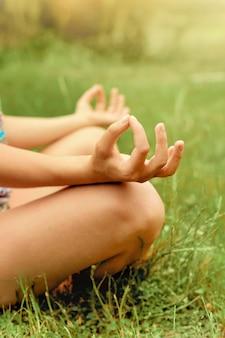 Hände schließen. frau machen yoga im freien. frau, die lebenswichtig und meditation für fitness-lifestyle-club am naturhintergrund im freien ausübt. gesundes und yoga-konzept