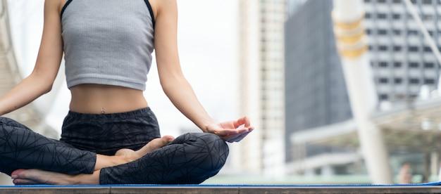 Hände schließen. frau tun das yoga, das in der stadt im freien ist. frau, die lebenswichtig und meditation für eignungslebensstil am freien in der stadt ausübt.