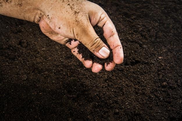 Hände schmutzig mit lehm, bodenhintergrund