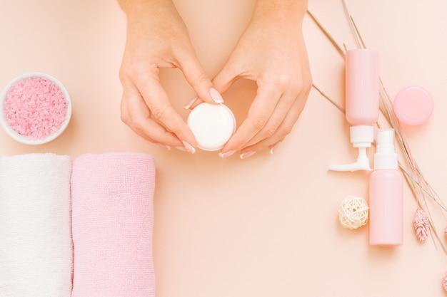 Hände schönheitspflege verschiedene kosmetische produkte auf korallenrosa