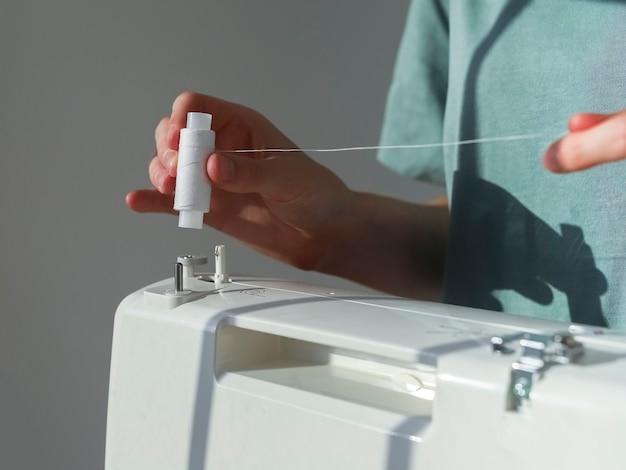 Hände setzen fadenspule auf nähmaschine