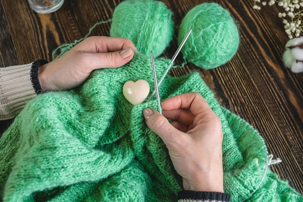 Hände stricken einen kuscheligen grünen pullover