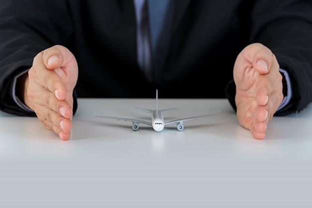 Hände stützen flugzeugmodell auf dem schreibtisch, schutzflugzeugsafe schützen sich
