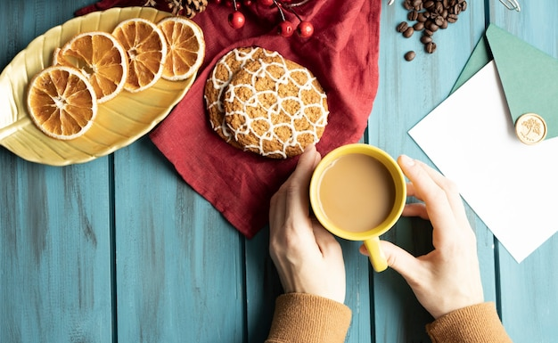 Hände, tasse cappuccino auf einem weihnachtstisch dekoriert