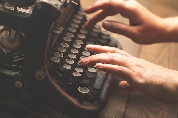 Hände tippen auf alter schreibmaschine, nahaufnahme