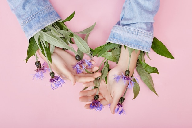 Hände und frühlingsblumen auf einer rosa tabellenhautpflege