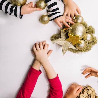 Hände und goldene weihnachtsverzierungen