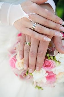 Hände und ringe auf hochzeitsblumenstrauß