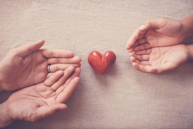 Hände und rotes herz-, krankenversicherungs-, spenden- und wohltätigkeitskonzept