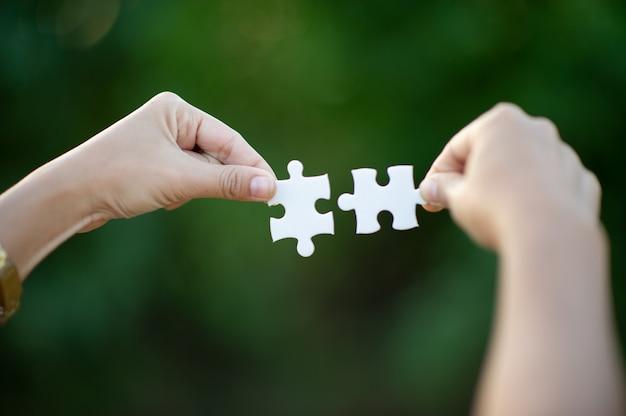 Hände und weiße puzzles nahaufnahmebild und integration geschäftskonzept und einheit