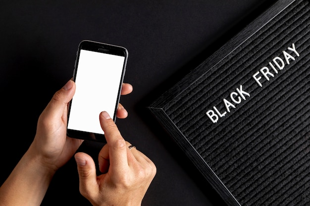 Hände unter verwendung des telefonspottes oben nahe bei schwarzem freitag-teppich