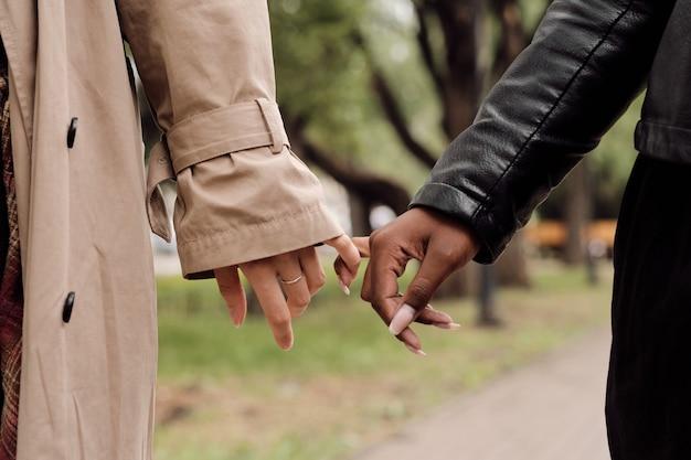 Hände von amourösen interkulturellen freundinnen, die im park spazieren gehen