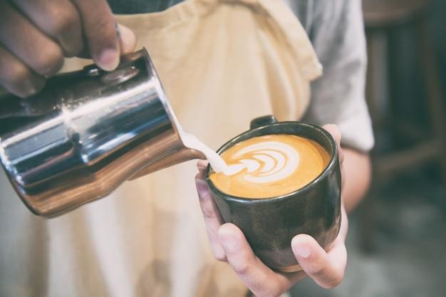 Hände von barista, der latte vorbereitet