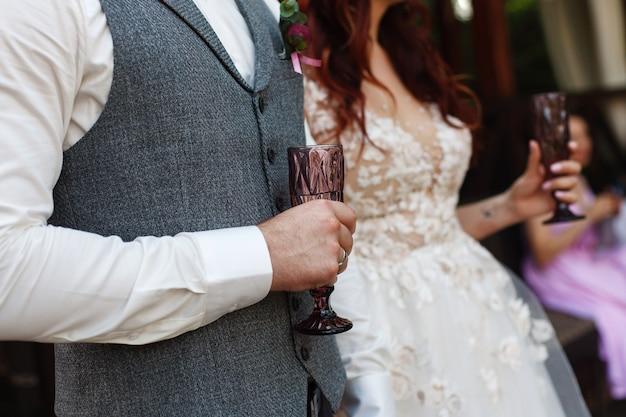 Hände von bräuten mit verzierten gläsern. zwei dekorierte gläser mit einem champagner in den händen von braut und bräutigam. 2 dekorierte weingläser. ort der feier hochzeit. hochzeit festlich