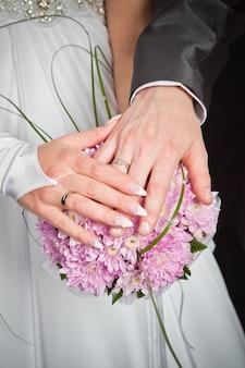 Hände von bräutigam und braut liegen auf hochzeitsblumenstraußhintergrund von rosa chrysanthemen