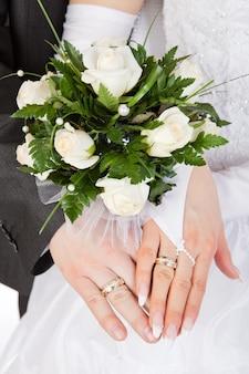 Hände von braut und bräutigam mit ringen und hochzeitsstrauß