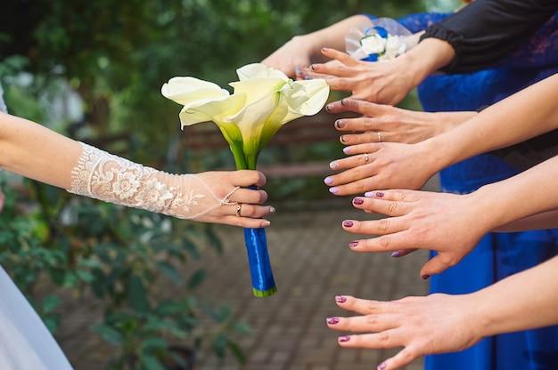 Hände von brautjungfern werden zu einem hochzeitsblumenstrauß von callas gezeichnet