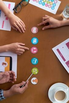 Hände von den unerkennbaren arbeitskollegen, die ikonen für projekt besprechen