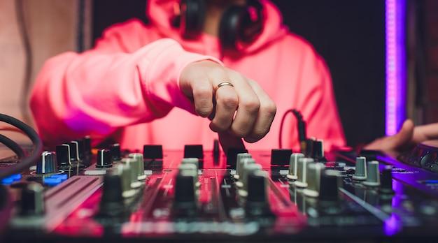 Hände von dj-mix-tracks auf digitalem plattenspieler und software auf laptop mit professioneller mixing-software. discjockey spielen musikshow.