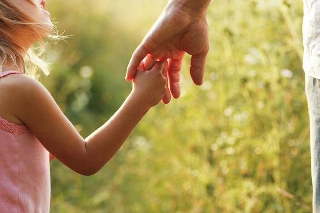 Hände von eltern und kind draußen im park